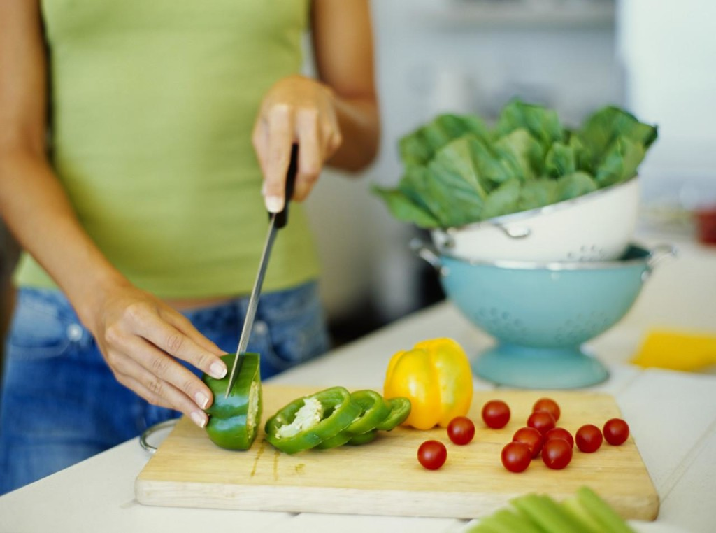 mid section view of a woman cutting vegetables --- Image by © Royalty-Free/Corbis